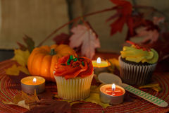Cupcakes with pumpkin and candles. Cupcakes with pumpkin, maple leaves, and candles decorations Royalty Free Stock Photography