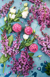 Cupcakes with purple lilac and white rose on blue table Stock Images