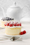 Cupcakes with raspberries and cream on table Stock Photography