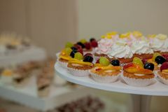 Cupcakes with raspberries, grapes and peach on a wedding table.  royalty free stock images