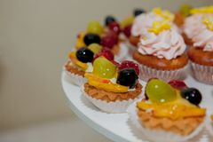 Cupcakes with raspberries, grapes and peach on a wedding table.  stock images