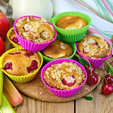 Cupcakes with rhubarb and cherries in tins on board Stock Image