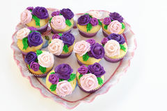 Cupcakes with Roses on Heart Platter. Decorated vanilla cupcakes with different shades of purple frosting roses on top, sitting on a heart shaped platter Stock Photos