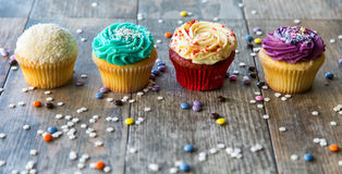 Cupcakes in a row on wooden table royalty free stock photo