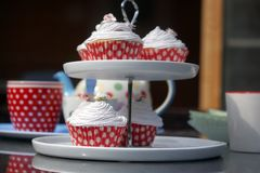 Cupcakes and tea, served in dotty cases on a cake stand. Cupcakes served with pink frosted cream and a pot of tea on a summers day stock images