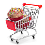 Cupcakes in a shopping cart. Some cupcakes topped with a chocolate frosting in a shopping cart on a white background royalty free stock images