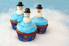 Cupcakes with snowmen. Chocolate cupcakes with vanilla frosting decorated with snowmen made of fondant and rolled in sugar Stock Photography