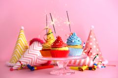 Cupcakes with sparklers. On color background stock images