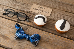 Cupcakes, spectacles, card, bow tie and spectacles on wooden plank Stock Photos