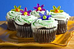 Cupcakes with sprinkles and plastic flowers Royalty Free Stock Image