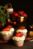 Cupcakes with strawberries on a dark background. Still life stock image