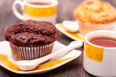 Cupcakes with tea on black wooden background Stock Images