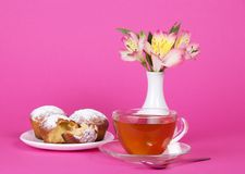 Cupcakes, tea and flowers in a vase Stock Images
