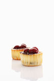 Cupcakes topped with chocolate cream and cherries Stock Photos