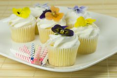 Cupcakes topped with edible flowers Stock Photo