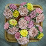 Cupcakes topped with rose shaped cream royalty free stock image