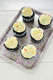 Cupcakes on tray. Chocolate cupcakes with white frosting on flowery tray Stock Photography