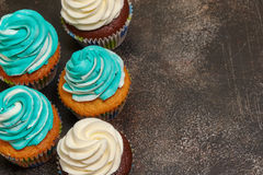 Cupcakes with turquoise and white buttercream frosting on brown background Stock Photos