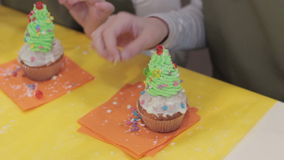 Cupcakes. Two little girls decorate muffins stock footage