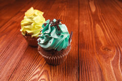 Cupcakes. Two cupcakes standing on wooden table Royalty Free Stock Image