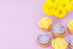Cupcakes verfraaide met gele en violette room en chrysanten op violette pastelkleurachtergrond voor groetkaart met copyscape Stock Afbeeldingen