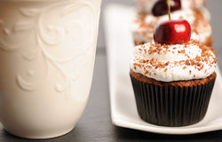 Cupcakes with whipped cream and cherry Stock Photos