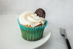 Cupcakes with white cheese cream decorated with cookies on a white plate stock image