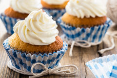 Cupcakes with white frosting. Gourmet cupcakes with white buttercream frosting on wooden table royalty free stock image