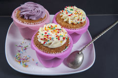 The cupcakes with white and violet cream with spoons on the black background Stock Images
