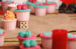 Cupcakes and wood block with 5 dot. Cupcakes in blur and two cupcakes in between is sharp and one of the fondant cupcake stand on wood block with 5 dot printed Royalty Free Stock Photos
