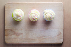 Cupcakes on Wood Overhead. Overhead shot of three cupcakes on a wooden chopping board, topped with swirls of buttercream icing and colourful sprinkles Stock Photography