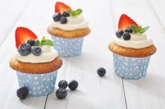 Cupcakes wordt verfraaid met en verse bessen die Stock Afbeeldingen