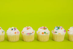 Cupcakes on yellow background Stock Photos