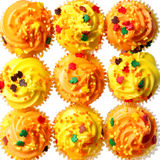 Cupcakes with yellow and orange frosting and colored sprinkles. Background. Sweet food for Halloween Royalty Free Stock Photos