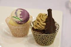 Cupcakevanille, chocolade, in decoratieve koppen Royalty-vrije Stock Afbeeldingen