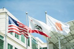Cupertino, CA, USA - March, 2015: flags in front of Apple Headqu. Arters with American Flag and flag with Apple icon. Apple is a multinational in  Silicon Valley Royalty Free Stock Photos