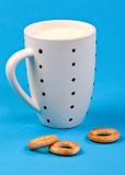 Cupful of milk and bread rings Royalty Free Stock Images