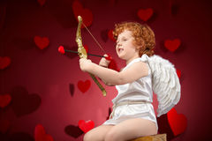 Cupid. Little boy in an image of the cupid on a red background stock photography