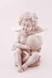 Cupid. Little angel with heart on light pink background Royalty Free Stock Image