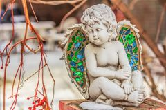 Cupid Angel Statue Sitting on a Brick Post. Ceramic cupid angel with stained glass in the wings sitting on a brick column beside an iron fence royalty free stock photo