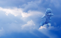 Cupid with arrow over cloudy sky Royalty Free Stock Photo
