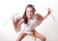 Cupid with bow and arrow. Humorous portrait of a cute six year old girl dressed as a cupid with white wings, bow and arrow, against studio background stock images