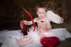 Cupid with Bow and Arrow. Cupid looking at his bow and arrow stock images