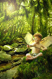 Cupid in fantasy forest. Little angel boy or cupid with wings and bow and arrow sitting on the mossy forest floor of a fantasy wood, aiming his arrow to shoot stock photo