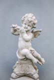 Cupid with Flute. A statue of a Cupid with Flute on the rooftop royalty free stock photo