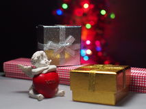 Cupid and gift box on background of bokeh Royalty Free Stock Photos