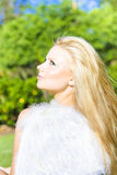Cupid, The Goddess Of Love. Beautiful young blonde woman in a green park wearing fluffy white feathered wings conceptual for Cupid the Goddess Of Love Stock Photography
