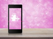 Internet online love connection, Valentines day concept. Cupid icon on modern smartphone screen on wooden table over blur pink background, Internet online love royalty free stock photography