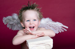 Cupid Laughing. Boy with Wings posing with pedistal, laughing stock photos