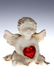 Cupid with red heart Stock Photography